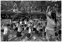 Schoolchildren doing gymnastics in  Singapore Botanical Gardens. Singapore ( black and white)