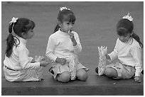 Three little girls in school uniform eating snack. Guadalajara, Jalisco, Mexico (black and white)