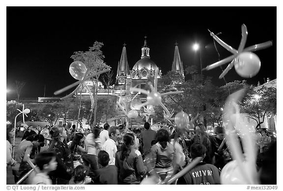 Children playing with ballons on Plaza de la Liberacion by night. Guadalajara, Jalisco, Mexico (black and white)