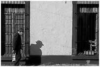 Elderly man walking along a colorful wall, Tlaquepaque. Jalisco, Mexico ( black and white)