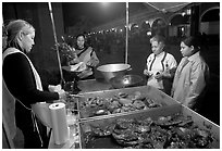 Women buying food at a food stand by night, Tlaquepaque. Jalisco, Mexico (black and white)