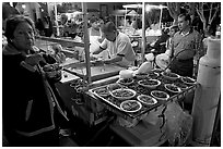 Woman eating by a street food stand , Tlaquepaque. Jalisco, Mexico (black and white)