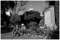 Men sitting in garden, with cathedral dome and ceramic monument, Tlaquepaque. Jalisco, Mexico (black and white)