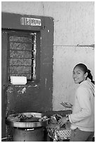 Woman preparing food outside a blue wall, Tonala. Jalisco, Mexico (black and white)