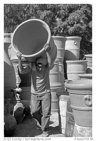 Man carrying a heavy pot, Tonala. Jalisco, Mexico (black and white)