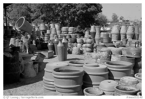 Pots for sale, with a man loading in the background, Tonala. Jalisco, Mexico (black and white)