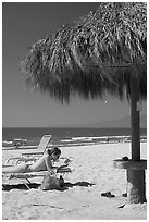 Woman in swimsuit reading on beach chair, Nuevo Vallarta, Nayarit. Jalisco, Mexico (black and white)