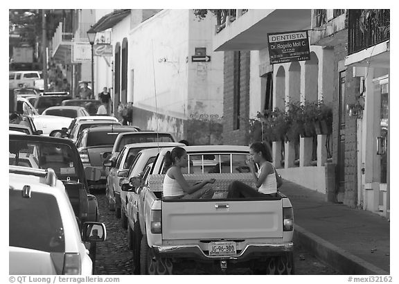 Young women riding in the back of a pick-up truck in a busy street, Puerto Vallarta, Jalisco. Jalisco, Mexico (black and white)