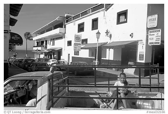 Girl riding in the back of pick-up truck in a street close to ocean, Puerto Vallarta, Jalisco. Jalisco, Mexico (black and white)