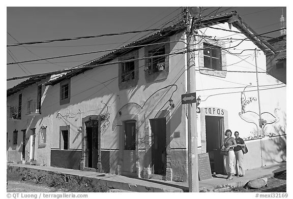 Two women outside of corner house with colorful door and window outlines, Puerto Vallarta, Jalisco. Jalisco, Mexico (black and white)
