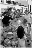 Children, mother, and balloon vendor , Puerto Vallarta, Jalisco. Jalisco, Mexico (black and white)