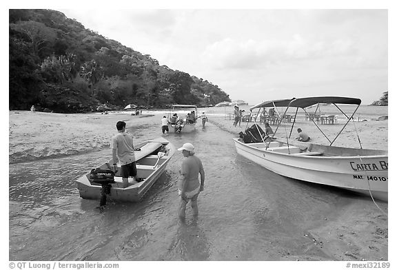 Boats moving from lagoon to ocean via small channel,  Boca de Tomatlan, Jalisco. Jalisco, Mexico (black and white)