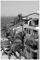 White adobe building with red tile roof,  palm trees and ocean, Puerto Vallarta, Jalisco. Jalisco, Mexico (black and white)