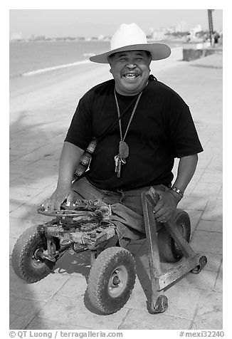 Man without legs  smiling on the Malecon, Puerto Vallarta, Jalisco. Jalisco, Mexico (black and white)