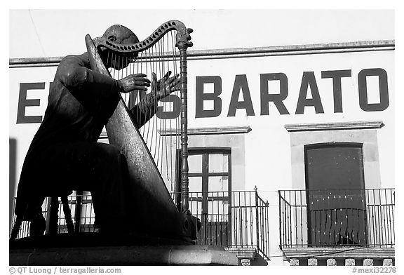 Statue of a musician and house with inscriptions. Zacatecas, Mexico (black and white)
