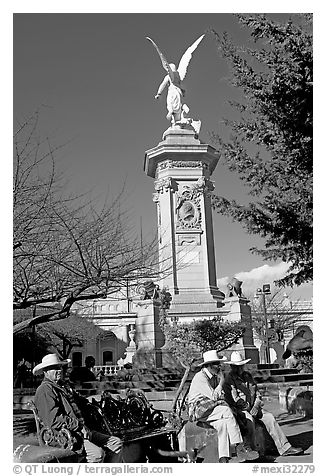 Men wearing cow-boy hats sitting in Garden of Independencia. Zacatecas, Mexico (black and white)