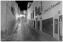 Uphill paved street by night with light trail. Zacatecas, Mexico (black and white)