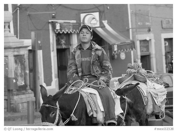 Young man riding a donkey in the streets. Guanajuato, Mexico (black and white)