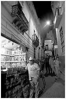 Man at a Newstand booth in a narrow callejone at night. Guanajuato, Mexico (black and white)