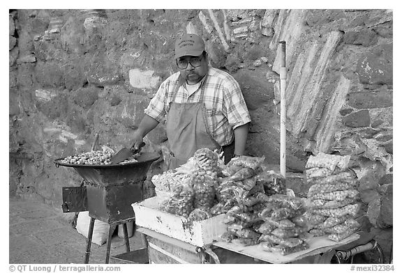 Man selling grilled peanuts on the street. Guanajuato, Mexico (black and white)