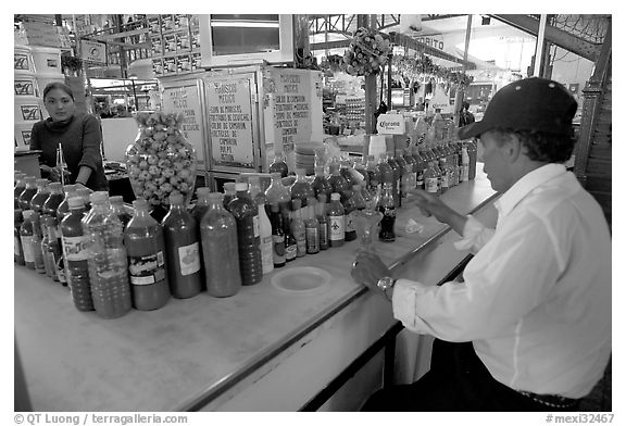 Man sitting at a booth offering a large variety of bottled chili. Guanajuato, Mexico