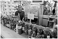 Woman at a booth with lots of chili bottles in Mercado Hidalgo. Guanajuato, Mexico (black and white)