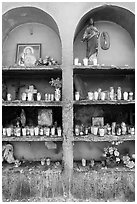 Candles, flowers, and religious offerings in a roadside chapel. Mexico (black and white)