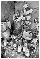 Religious figures and candles in roadside chapel. Mexico (black and white)