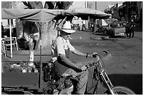 Man with cigarette riding a motorcycle-powered food stand on town plaza. Mexico (black and white)