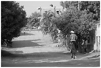 Man on horse going down a village street. Mexico (black and white)