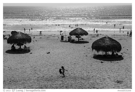 Straw sun shelter umbrellas and ocean, Ensenada. Baja California, Mexico (black and white)