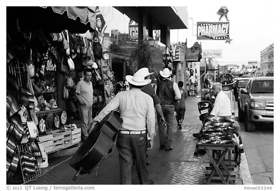 Musicians walking on street, Ensenada. Baja California, Mexico (black and white)