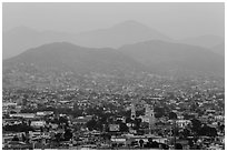 Distant view of Ensendada spreading up hills at sunset. Baja California, Mexico (black and white)