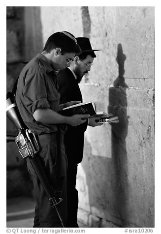 Young soldier and orthodox jew reading prayer  books at the Western Wall. Jerusalem, Israel