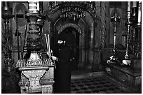 Christian Orthodox priest lighting candles. Jerusalem, Israel ( black and white)