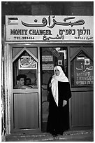Muslem woman exiting a money changing booth. Jerusalem, Israel (black and white)