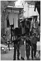Children in a busy old town alley. Jerusalem, Israel ( black and white)