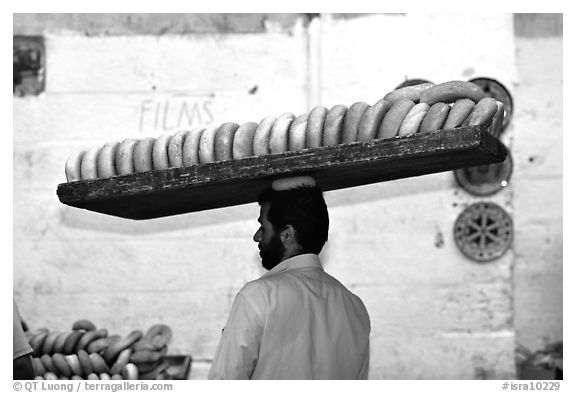 Man carrying many loafes of bread on his head. Jerusalem, Israel (black and white)