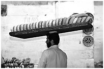 Man carrying many loafes of bread on his head. Jerusalem, Israel ( black and white)