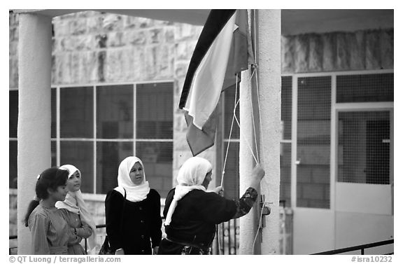 Women raise the Palestian flag at a school in East Jerusalem. Jerusalem, Israel (black and white)