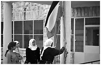 Women raise the Palestian flag at a school in East Jerusalem. Jerusalem, Israel ( black and white)