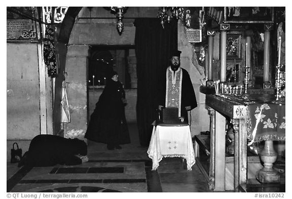 Worshiping inside the Church of the Holy Sepulchre. Jerusalem, Israel (black and white)