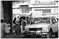 Women next to an old French Peugeot car, Hebron. West Bank, Occupied Territories (Israel) (black and white)