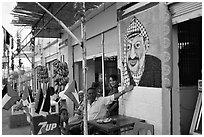 Palestinian cafe owner pointing proudly to a painting of Yasser Arafat, Jericho. West Bank, Occupied Territories (Israel) (black and white)
