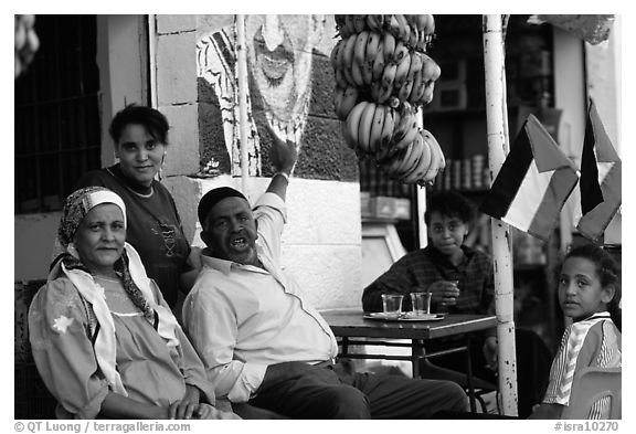 Palestinian head of family  pointing  to a mural of Yasser Arafat, Jericho. West Bank, Occupied Territories (Israel) (black and white)
