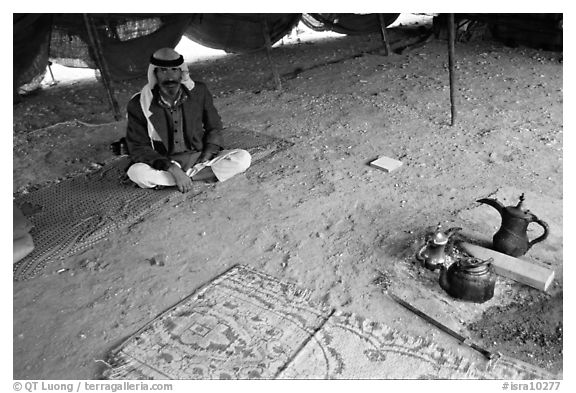 Bedouin man sitting on a carpet in a tent, Judean Desert. West Bank, Occupied Territories (Israel) (black and white)
