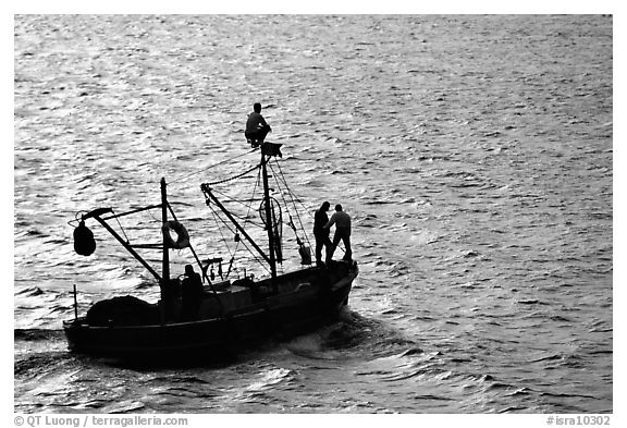 Small fishing boat silhouetted, late afternoon, Akko (Acre). Israel (black and white)