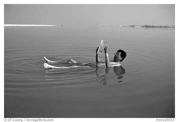 Visitor reading while floating in the Dead Sea. Israel (black and white)