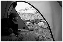 Visitor in  tent looking outside to Lamplugh Glacier. Glacier Bay National Park, Alaska (black and white)