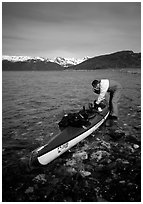 Kayaker tying up gear on top of the kayak,  East Arm. Glacier Bay National Park, Alaska (black and white)